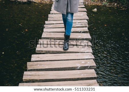 Young woman crossing a wooden bridge