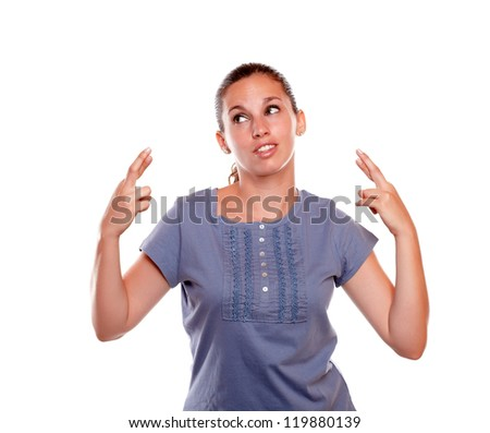 Young woman crossing her fingers making a wish while is looking to her right on blue blouse on isolated background - copyspace - stock photo