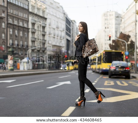 Young woman crossing the street in the city
