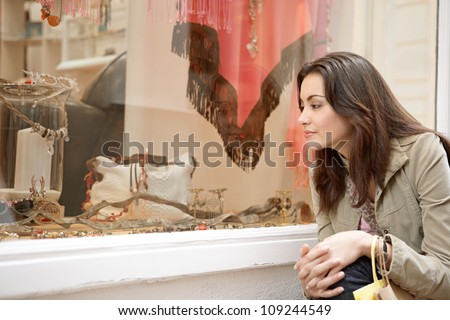 Young woman crouching down a shop window to look at a product, smiling.