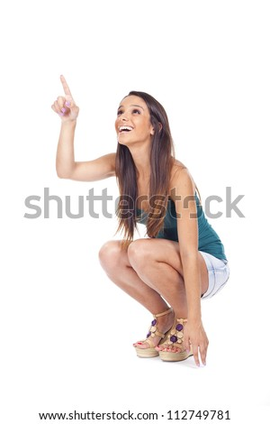 Young woman crouching with his finger pointing to smile... - stock photo