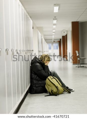 Young woman crying by the lockers at school - stock photo
