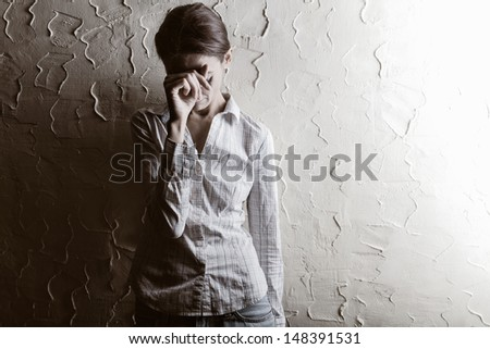 Young woman crying in wall - stock photo