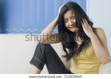 Young woman crying on a couch with her head in her hand