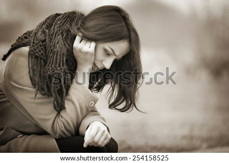Young Woman Crying Outdoors in the Dark Autumn Day - stock photo