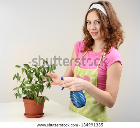 Young woman cultivating flowers on grey background - stock photo