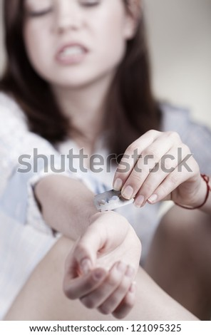 Young woman cuts veins on a hand on light background. Focus on hand