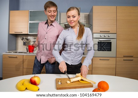 Young woman cutting banana with a sly glance in front of her boyfriend cast an intimidated glance - stock photo