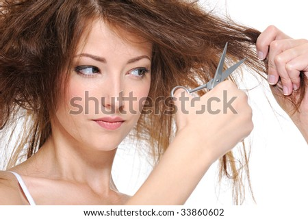 young woman cutting her backcombing brunette hair - close-up - stock photo