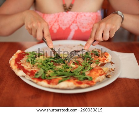 Young woman cutting pizza in restaurant - stock photo