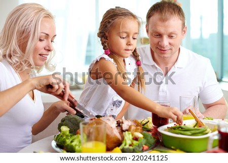 Young woman cutting roasted turkey while her daughter taking garnish and her husband looking at it  - stock photo