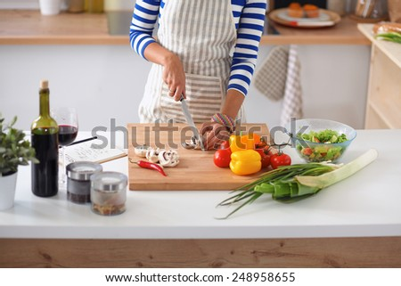 Young woman cutting vegetables in kitchen - stock photo
