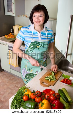Young woman cutting vegetables in the kitchen.  Pretty girl in is cooking in the kitchen. home life: woman preparing something to eat. Smiling female standing and cutting cucumber in the kitchen. - stock photo