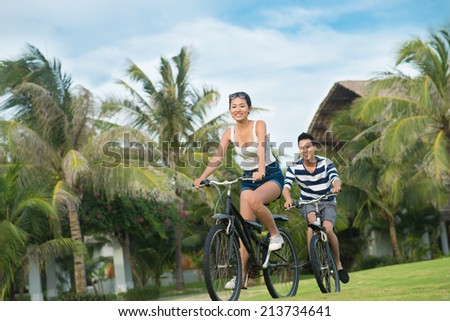 Young woman cycling in the park with her boyfriend - stock photo