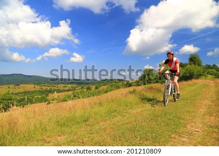 Young woman cycling on grass covered trail