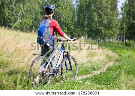 young woman cyclist going  to the park - stock photo
