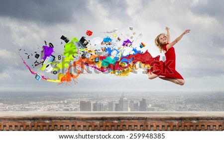 Young woman dancer in red dress jumping high