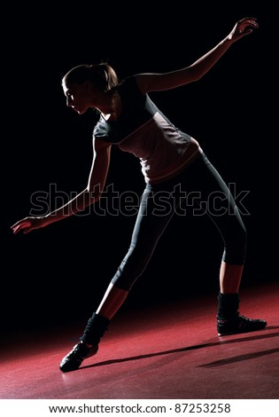 Young woman dancer. On black wall background silhouette shot