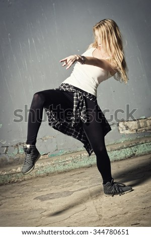 Young woman dancer on graffiti background. Dancing and urban culture concept. Film grain effest    - stock photo