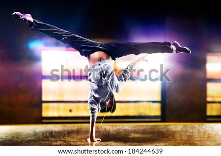 Young woman dancer on urban background.