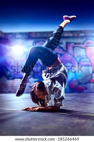 Young woman dancer on urban background. - stock photo