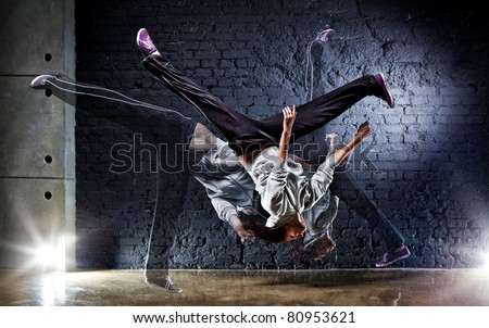 Young woman dancer on wall background. - stock photo