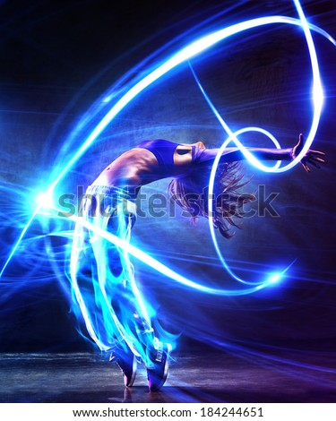Young woman dancer. With light effects.