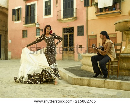 Young woman dancing and a mid adult man playing the guitar - stock photo