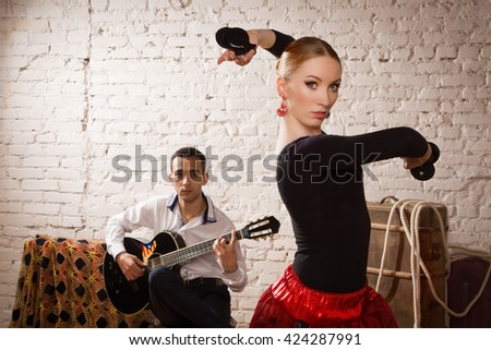 Young woman dancing flamenco in traditional flamenco dress and a man playing the guitar
