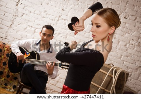 Young woman dancing flamenco in traditional flamenco dress and a man playing the guitar - stock photo