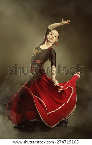 young woman dancing flamenco on black - stock photo