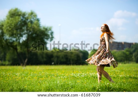 Young woman dancing happy in summer meadow - stock photo