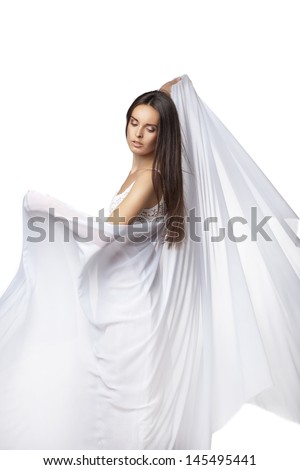 Young woman dancing in gorgeous white dress over white - stock photo