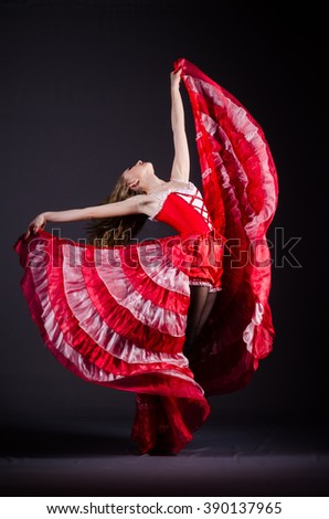 Young woman dancing in red dress - stock photo