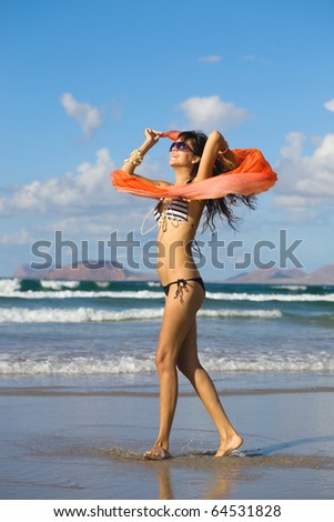 young woman dancing with kerchief against the blue sky on the beach