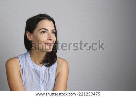 Young woman daydreaming with a lovely smile of pleasure as she stares into the air reminiscing good memories, on a graduated grey background with copyspace - stock photo