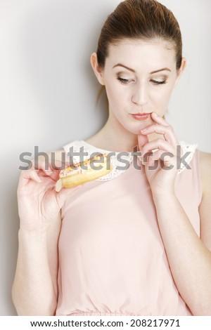 Young woman deciding whether to eat an unhealthy doughnut expressing guilt. - stock photo