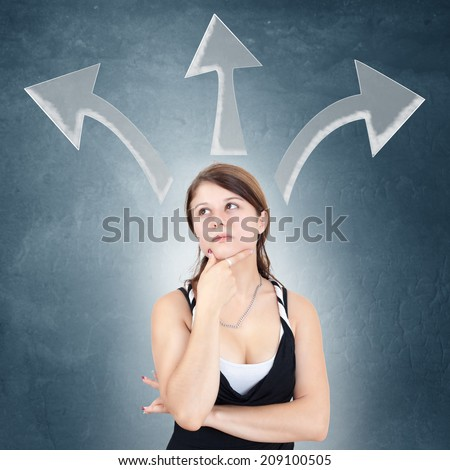 Young woman deciding with drawn arrows above her head - stock photo