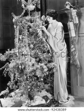 Young woman decorating a Christmas tree - stock photo
