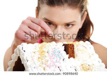 Young woman decorating gingerbread house model - stock photo