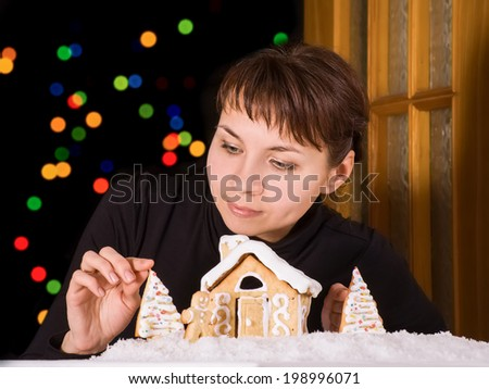 Young woman decorating the toy scene with homemade gingerbread house and man. Christmas and New Year