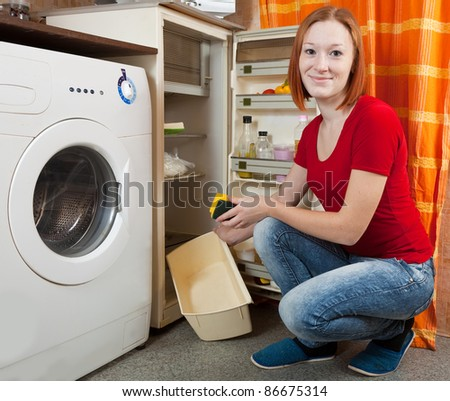 Young woman  defrosting the refrigerator at her kitchen