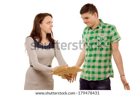 Young woman demanding an explanation from her boyfriend as she points to a batch of papers she is holding, but he just shrugs in ignorance, isolated on white - stock photo
