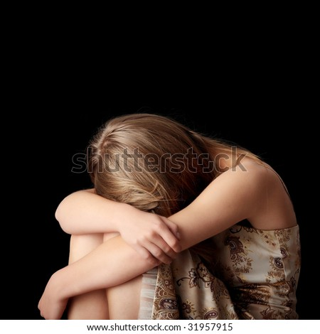 Young woman depression isolated on black background - stock photo
