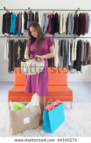 Young woman digging through purse in clothing store - stock photo