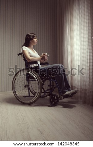 Young woman disabled with a cup of tea looking out a window - stock photo