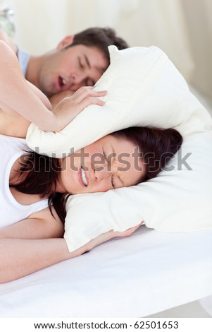 Young woman disturbed by the snores of her boyfriend in the bedroom at home - stock photo