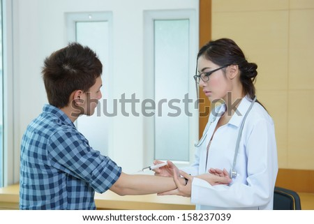 Young woman doctor giving male patient injection in office room