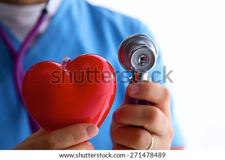 Young woman doctor holding a red heart, isolated on white background - stock photo