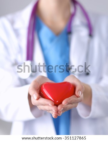 Young woman doctor holding a red heart, standing on gray background - stock photo